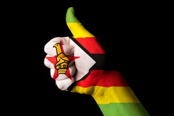 Hand with thumb up gesture in colored zimbabwe national flag as symbol of excellence, achievement, good, - for tourism and touristic advertising, positive political, social management of country