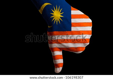 Hand with thumbs down gesture in colored malaysia national flag as symbol of negative political, cultural, social management of country