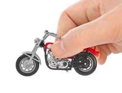 Hand with toy motorbike isolated on white background