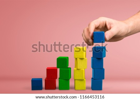 Hand with toy wooden blocks stack, towers of blank multicolor box cubes over white background #1166453116