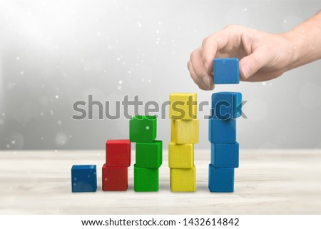 Hand with toy wooden blocks stack, towers of blank multicolor box cubes over white background #1432614842