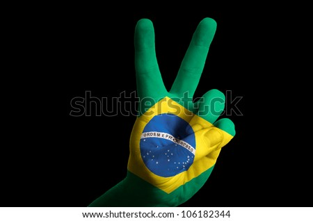 Hand with two finger up gesture in colored brazil national flag as symbol of winning,  - for tourism and touristic advertising, positive political, cultural, social management of country