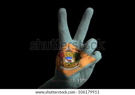 Hand with two finger up gesture in colored delaware state flag as symbol of winning, - for tourism and touristic advertising, positive political, cultural, social management of country