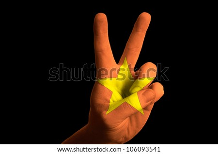 Hand with two finger up gesture in colored vietnam national flag as
