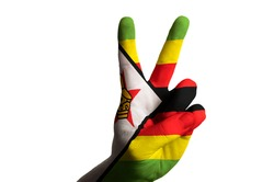 Hand with two finger up gesture in colored zimbabwe national flag as symbol of winning,  - for tourism and touristic advertising, positive political, cultural, social management of country