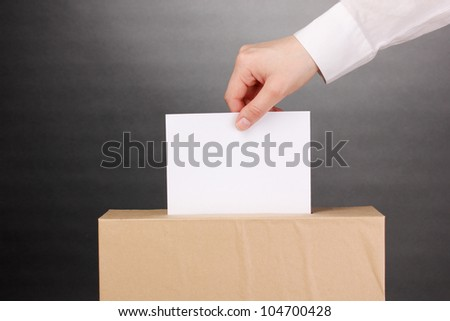 Hand with voting ballot and box on grey background