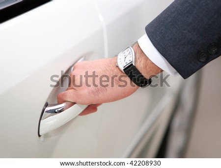 hand with watch opening luxury car door