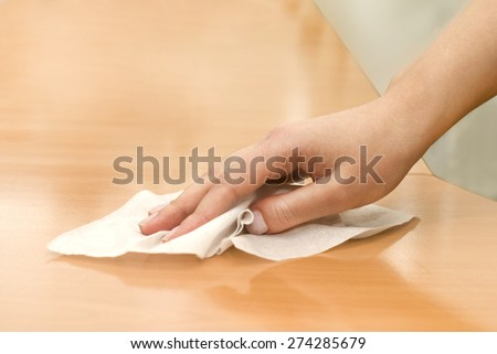 hand with wet wipe cleaning table