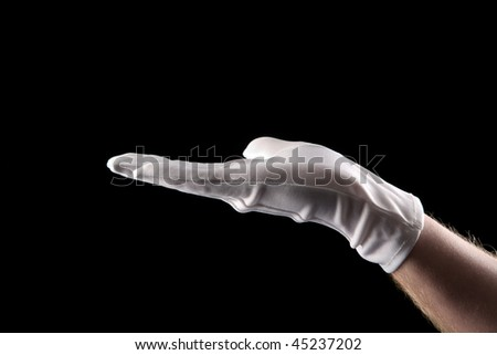 hand with white glove isolated before black background ready to hold your message