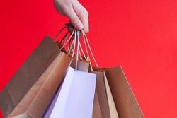 Hand with white paper bags and craft on bright red background. Season of sales or purchases as gift for holidays. Christmas shopping. Courier delivery of products in eco-friendly packaging