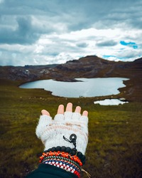 Hand with wool glove and bracelets pointing to a beautiful lagoon in the mountains of Latin America Peru