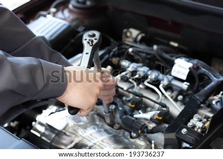 Hand with wrench. Auto mechanic in car repair #193736237