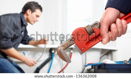 Hand with wrench. Plumber. Plumbing service concept.
