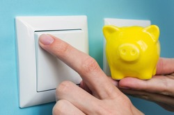 Hand with yellow piggy bank turns OFF electric lights at home. Savings on power supply, on utilities. Symbolic image.