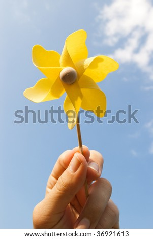 hand with yellow pinwheel on clear blue sky