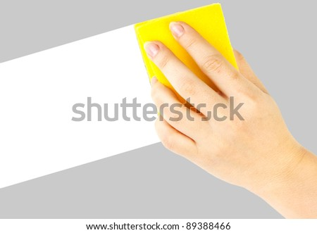 Hand with yellow sponge on white background