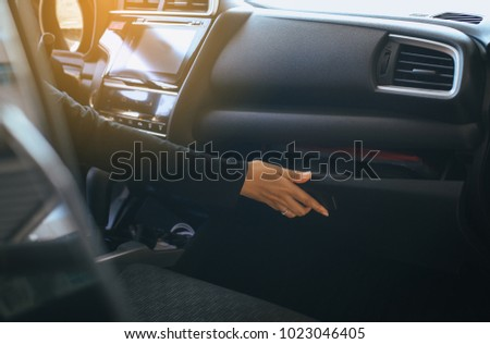 Hand woman open glove compartment box in car