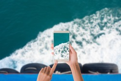 Hand woman Taking sea soft wave photo with mobile. hand woman holding mobile with blue sea soft wave view on blur image of  sea soft wave on top view. sea travel summer hollidays concept.