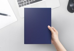 Hand women holding book cover blank on office table top view.  Blank book cover.