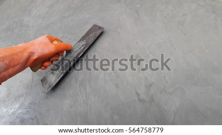 Hand worker hold trowel on cement loft wall