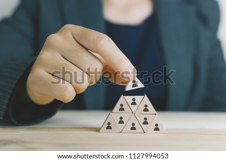 Hand working woman putting wood cube block on top pyramid,Human resources, social networking, assessment center concept, personal audit or CRM concept - recruiter complete  #1127994053