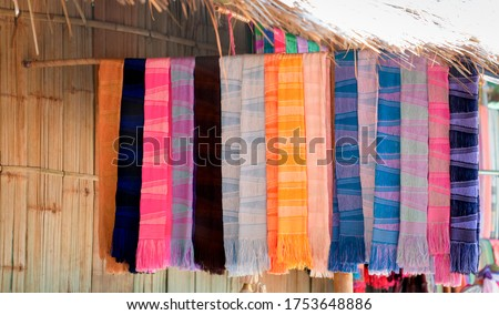 Hand-woven cloth, Khor hill tribe, hung in front of the house Colorful hand-woven cloth hanging, Khor hill tribe, hung in front of the house. Tribal dress at hill tribe village. Thailand - CHIANG Rai,