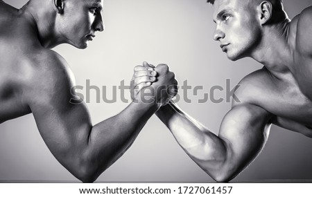 Hand wrestling, compete. Hands or arms of man. Muscular hand. Clasped arm wrestling. Two men arm wrestling. Rivalry, closeup of male arm wrestling. Two hands. Muscular men measuring forces, arms.