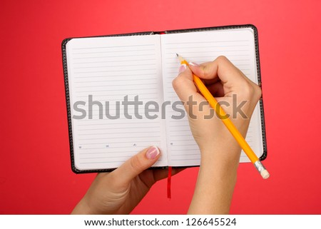 Hand write on notebook, on color background - stock photo