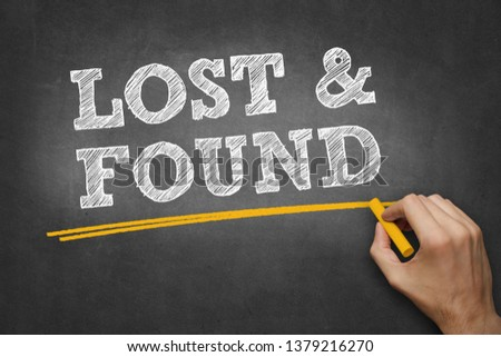 hand writes chalk text on blackboard - LOST and FOUND