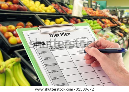Hand Writing a Diet Plan by Supermarket Fruit
