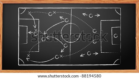 Hand writing a soccer game strategy on a blackboard. - stock photo