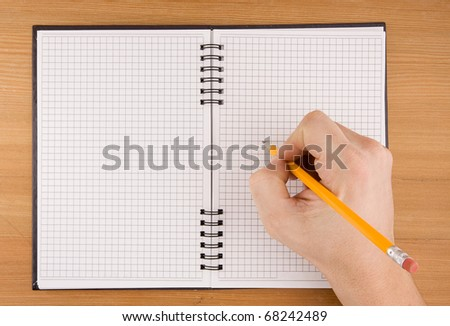 hand writing by pencil on checked notebook