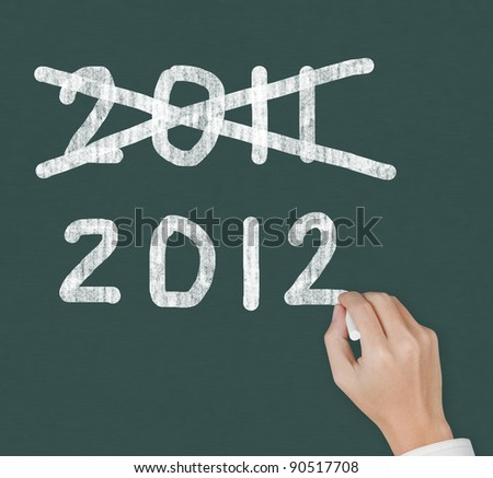 hand writing cross mark on 2011 and new year 2012 on chalkboard