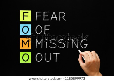 Hand writing FOMO - Fear Of Missing Out with white chalk on blackboard.