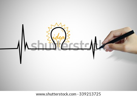hand writing heartbeat with light bulb idea , business idea , business concept ,Innovation concept