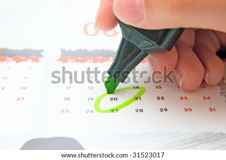 Hand writing important date in calendar