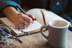 Hand writing in journal with coffee mug