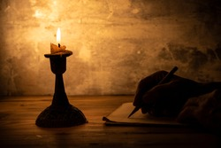 hand writing letter with pencil on paper in candle light condition