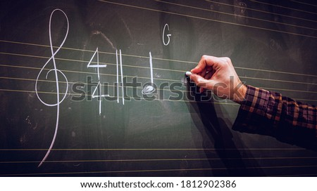 Hand writing music notes on a score on blackboard with white chalk. Musical composition or training or education concept. ストックフォト ©