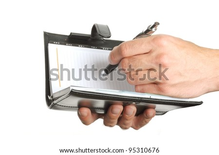 hand writing notes into a personal organizer isolated on white background