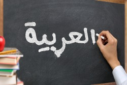 Hand writing on a blackboard in a  Arabic language learning class course with the text