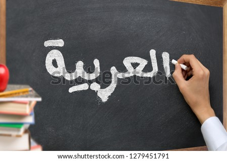 "Hand writing on a blackboard in a Arabic language learning class course with the text ""Arabic"" written on it. with Some books and school materials concept."