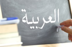 Hand writing on a blackboard in a language class with the text