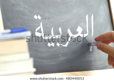 "Hand writing on a blackboard in a language class with the text ""Arabic"" written on it. Some books and school materials."