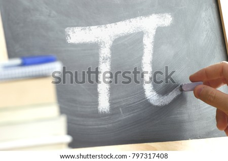 Hand writing on a blackboard in a Math class with the PI symbol written on. Some books and school materials.