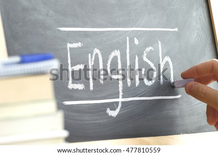 """Hand writing on a blackboard in an language class with the word """"English"""" wrote in. Some books and school materials."""