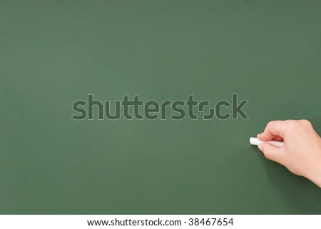 Hand writing on a blank blackboard with white chalk.