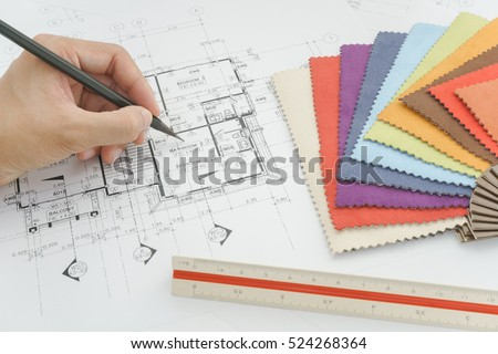 Hand writing on architectural plan with fabric sample on interior designer working table