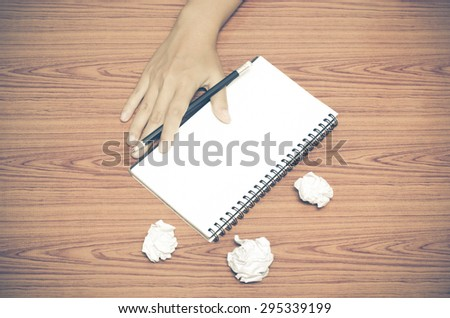 hand writing on notebook with crumpled paper on wood table background vintage style