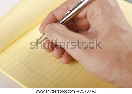 hand writing on yellow page with a silver colored pen